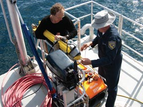 Co-principal investigator Roger Hanlon holds the sidescan sonar while California Department of Fish and Game Captain Raymond Michalski, attaches a video camera to the vehicle. The camera allows for visual ground-truthing while the sonar registers echoes from the seafloor and benthic organisms such as squid egg beds. The surface vessel platform is R/V Shearwater, owned and operated by the NOAA Chanel Islands National Marine Sactuary in Santa Barbara, CA. Photo by Ken Foote, WHOI.
