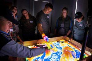 Teachers explore Zephyr's Augmented Reality Sandbox.